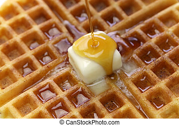 pouring maple syrup over homemade american round waffles...