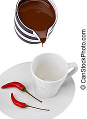 pouring melted chocolate in a cup with red chili on plate