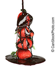 Pouring melted chocolate over four strawberries