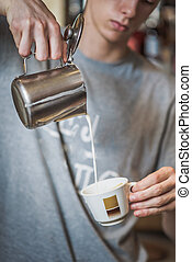 Pouring milk in a espresso coffee cup