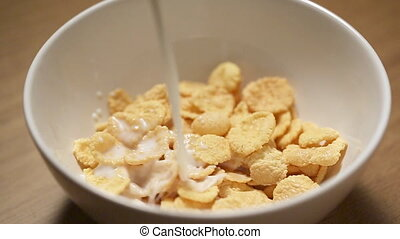 Pouring milk in bowl with corn flakes