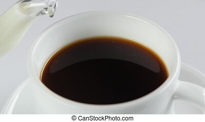 Pouring milk into cup with coffee on a white background, slow motion, close up