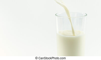 Pouring milk into glass isolated on white background.