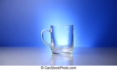 Pouring milk - Milk being poured in glass on blue background