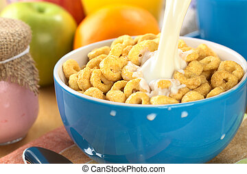Pouring milk over a bowl full of honey flavored cereal loops (Selective Focus, Focus on the milk stream)