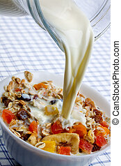 Pouring milk over muesli with dried fruit - Pouring fresh...