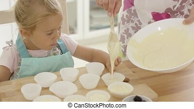 Pouring muffin batter into holders - Excited child pointing ...