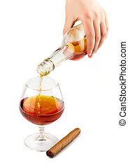 Pouring of cognac in glass with cigar isolated on white