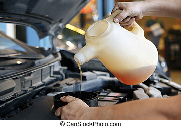 Pouring oil to car engine,