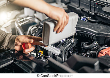 Pouring oil to car engine, closeup