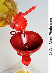 Pouring olive oil through funnel. - Pouring olive oil...