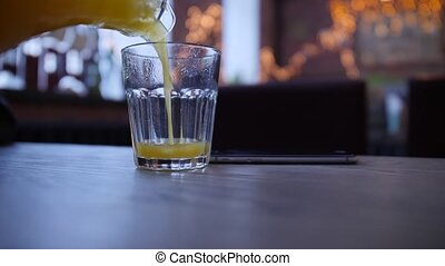 Pouring orange juice into glass on the table