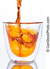 pouring orange water in to clear glass