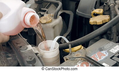 Pouring pink windshield washer fluid into the car