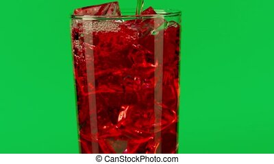 Pouring red drink into a glass with ice cubes against green background, close-up slow motion shot on Red
