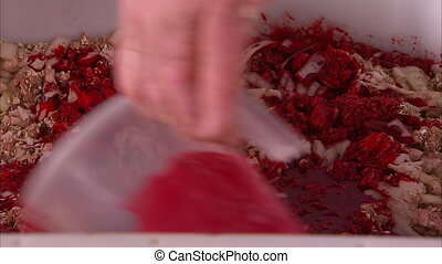 Pouring red sauce to meat in close up