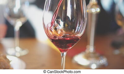 Pouring red wine from bottle into glass. Wine degustation.