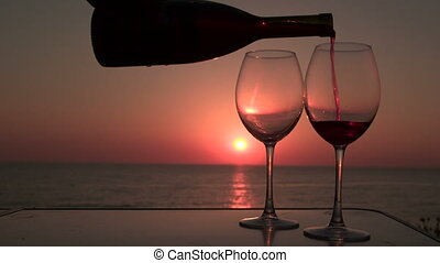 Pouring red wine in two glasses at sunset near the sea