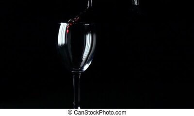 Pouring red wine into a wine glass super slow motion video, black background
