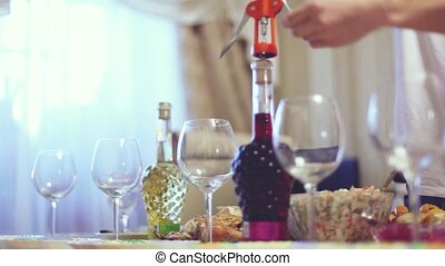 Pouring red wine into glass on served table - Pouring red...