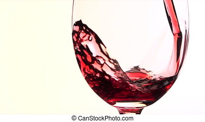 Pouring red wine into the glass against white background,...