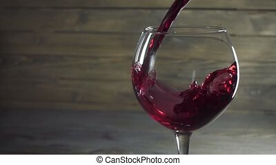 Pouring red wine into the glass against wooden background....