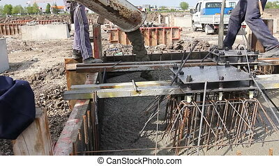 Pouring reinforced concrete in foundation mold - Workers at...