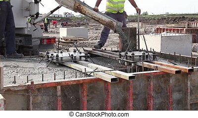 Pouring reinforced concrete. - Workers at building site are...