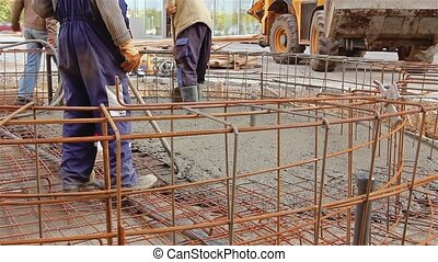 Pouring reinforced concrete - Workers at building site are...