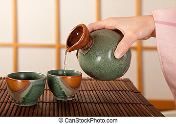 Pouring sake - Female hand pouring two cups of japanese sake