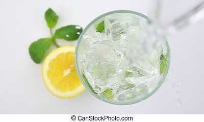 Pouring Soda into a Glass with the Ice Cubes.