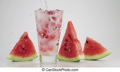 Pouring Soda Water into a Glass with the Ice and Watermelon Cubes