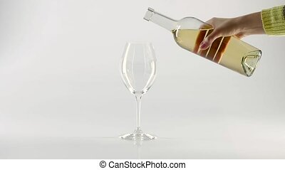 Pouring sparkling white wine into a wineglass with bottle, white, slowmotion