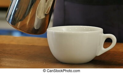 Pouring stream milk into a cup of hot coffee. Close up. Slow...