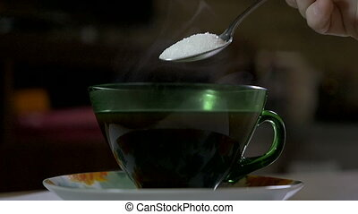 Pouring sugar in a cup of coffee