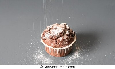 Pouring sugar on a chocolate muffin on a gray table...