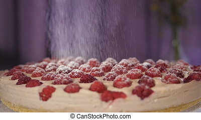 Pouring sugar powder on a cake - through a sieve of sifted...