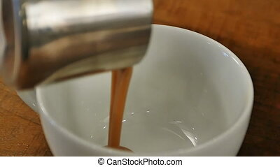 Pouring sweet caramel syrop for coffee. Close up. Slow...