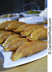 Pouring Syrup on Qatayef, Arabic Sweets with Nuts for Ramadan and Eid