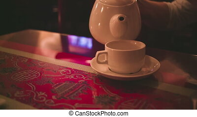 Pouring tea in a cup on table.
