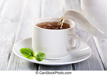 Pouring tea into cup of tea
