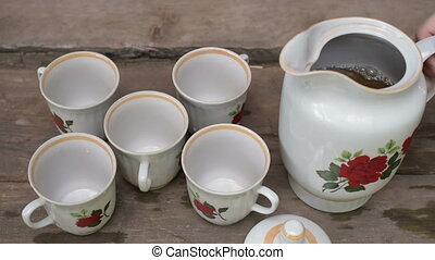 Pouring tea into five mugs
