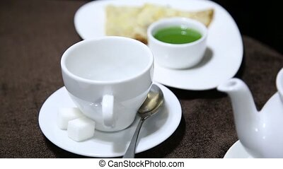 Pouring tea into white cup on table from porcelain kettle. jelly and pancake on a background
