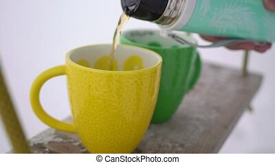 Pouring tea to cup from thermos outdoors at winter