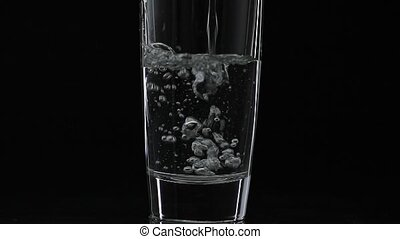 Pouring up shot of vodka into drinking glass. Slow motion....
