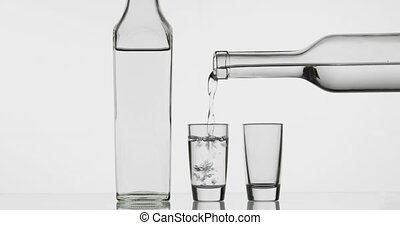 Pouring up two shot of vodka from a bottle into glass. White...