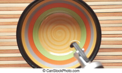 Pouring vegetable oil into a bowl on table ,
