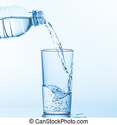Pouring water from bottle into glass on blue background.