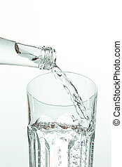 Pouring water from bottle into glass on white