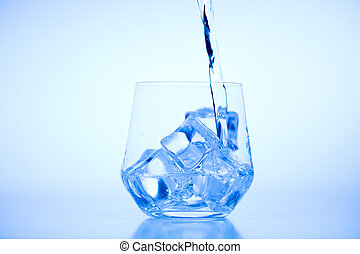 Pouring water from plastic bottle into a glass with ice on light blue background